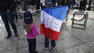 """Des enfants portent un drapeau """"Je soutiens papa et maman"""", lors d'une manifestation de soutien à la police à Evry (Essonne), samedi 22 octobre. (THOMAS SAMSON / AFP)"""
