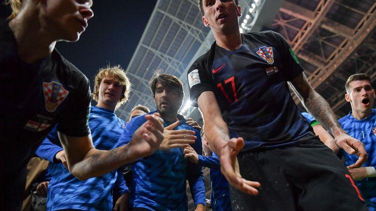 Mario Mandzukic (au centre) offre son aide au photographe de l'AFP Yuri Cortez, après que celui-ci a été renversé par les joueurs de la Croatie lors de la célébration de leur deuxième but face à l'Angleterre (2-1), le 11 juillet. (YURI CORTEZ / AFP)