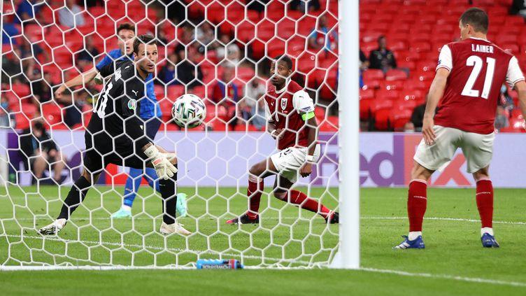 Le gardien de l'Autriche Daniel Bachmann s'incline en prolongation face à l'attaquant italien Federico Chiesa, le 26 juin 2021 à Londres. (CARL RECINE / POOL / REUTERS POOL)