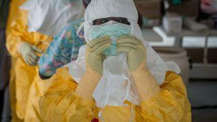 Des membres de Médecins sans frontières s'équipent avant de pénétrer dans le centre de traitement d'Ebola, mis en place dans les faubourgs de Monrovia (Liberia), jeudi 16 octobre 2014. (MOHAMMED ELSHAMY / ANADOLU AGENCY / AFP)