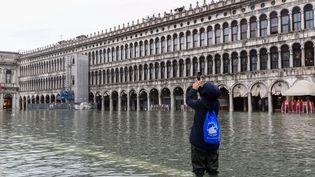 Un touriste prend une photo de la place Saint-Marc inondée, le 24 novembre 2019 à Venise (Italie). (MIGUEL MEDINA / AFP)