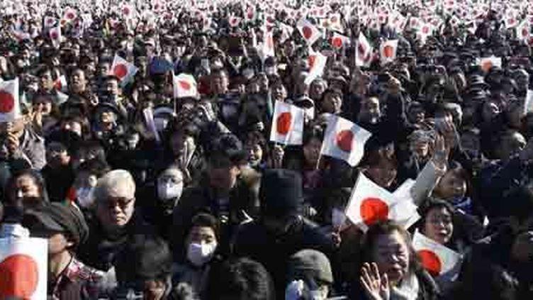 Des citoyens japonais agitent le drapeau national pendant une apparition de l'empereur Akihito et sa famille au palais impérial à Tokyo, à l'occasion du Nouvel an, le 2 janvier 2014. (Reuters - Yuya Shino)