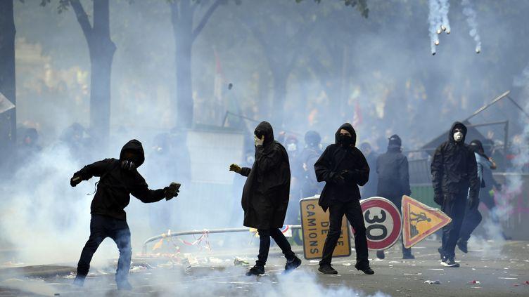 Un manifestant lance une pierre alors que des nuages de gaz lacrymogènes se lèvent lors d'une manifestation en marge d'unemanifestation du1er-Mai, à Paris,en 2018. (ALAIN JOCARD / AFP)
