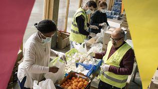 Les professionnels de l'association Aurore distribuent des repas dans la cour dans le 14e arrondissement de Paris, le 2 avril 2020. (DENIS MEYER / HANS LUCAS / AFP)