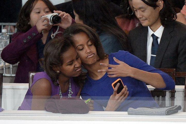"""Sasha (à gauche) et Malia Obama posent pour un """"selfie"""" durant la cérémonie d'investiture de leur père, le 21 janvier 2013 à Washington (DC). (JOE KLAMAR / AFP)"""