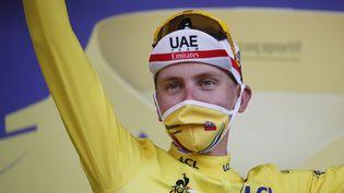 Le Slovène Tadej Pogacar fête son maillot jaune de leader du classement général sur le podium après avoir remporté la 20e étape de la 107e édition du Tour de France, un contre-la-montre de 36 kilomètres entre Lure et La Planche des Belles Filles (Haute-Saône), le 19 septembre 2020. (SEBASTIEN NOGIER / AFP)