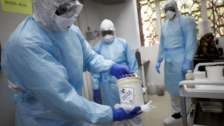 """Un chercheur malien tient un échantillon à tester dans le laboratoire de l'hôpital """"Point-G"""" de Bamako, le 19 mars 2020. (MICHELE CATTANI / AFP)"""