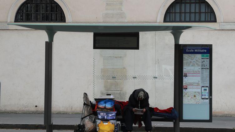 Un sans-abri, assis à un abri-bus, le 22 mars 2020 à Paris. Photo d'illustration. (LUDOVIC MARIN / AFP)