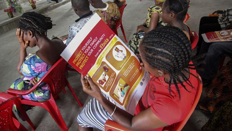 (Dimanche dernier, à Monrovia, au Liberia. Une femme lit les consignes sanitaires édictées par l'UNICEF © MaxPPP)