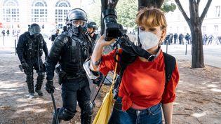 La photographe Marie Rouge repoussée et tenue à distance par des policiers pour ne pas prendre de clichés d'une arrestation, lors d'une manifestation de soignants, le 16 juin 2020 à Paris. (AMAURY CORNU / HANS LUCAS / AFP)