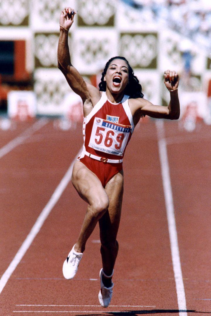 L'Américaine Florence Griffith-Joyner lève les bras après avoir établi le nouveau record olympique et remporté la médaille d'or sur le 100 m, lors des JO de Séoul, le 25 septembre 1988. (RON KUNTZ / IOPP / AFP)