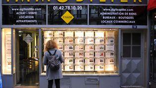 Une femme consulte des annonces immobilières, le 23 novembre 2017, à Paris. (SERGE ATTAL / ONLY FRANCE / AFP)
