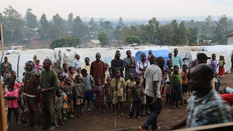 Des réfugiés se tiennent devant des tentes dans un camp de personnes déplacéesà l'extérieur de la ville de Bunia, dans la province d'Ituri (République démocratique du Congo), le 21 juin 2019. (SAMIR TOUNSI / AFP)