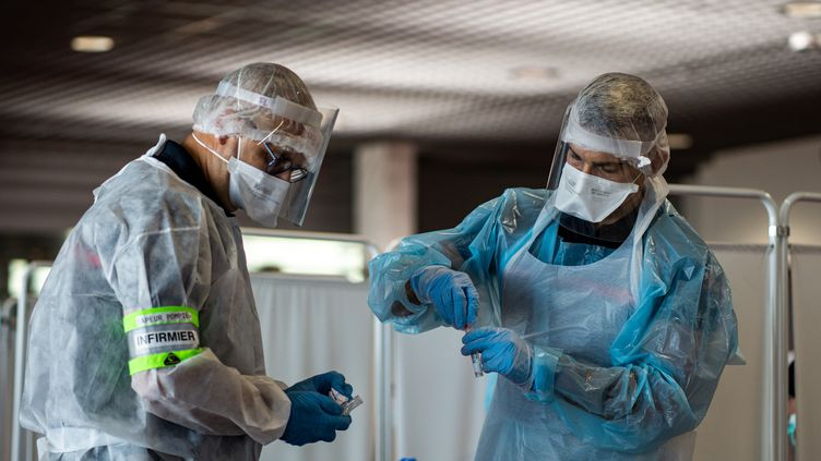 Des infirmiers prélèvent des échantillons sur des passagers à leur arrivée de Turquie, le 11 août 2020 à l'aéroport de Lyon. (NICOLAS LIPONNE / HANS LUCAS / AFP)