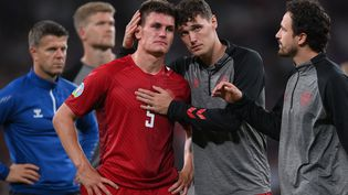 Joakim Maehle (en rouge) consolé par ses coéquipiers après l'élimination du Danemark en demi-finale de l'Euro 2021 par l'Angleterre mercredi 7 juillet à Wembley. (LAURENCE GRIFFITHS / AFP)