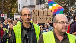"""Des """"gilets jaunes"""" défilent en solidarité avec les manifestants chiliens, le 26 octobre 2019 à Paris. (AMAURY CORNU / HANS LUCAS / AFP)"""