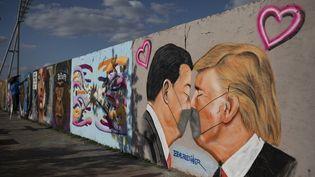 Le baiser masqué en temps de coronavirus du président chinois Xi Jinping et de son homologue américain Donald Trump, une oeuvre signée Eme Freethinker réalisée sur ce qu'il reste du mur de Berlin. Photo datée du 26 avril 2020. (MAJA HITIJ / GETTY IMAGES EUROPE)