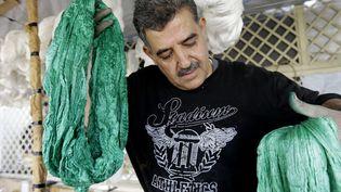 Mohamed al-Rihaoui sort des fils de soie de la teinture  (LOUAI BESHARA / AFP)