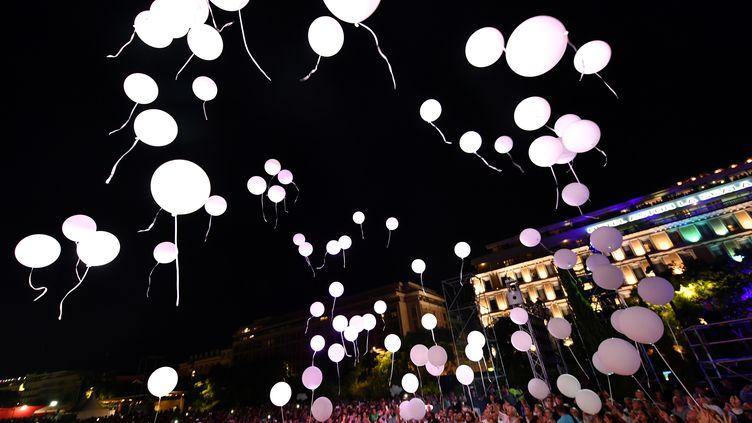 Quatre-vingt six ballons sont lâchés dans le ciel de Nice en hommage aux 86 victimes de l'attentat survenu un an plus tôt, vendredi 14 juillet 2017. (YANN COATSALIOU / AFP)