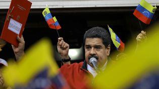 Le président vénézuélien Nicolas Maduro brandit devant ses partisans un décret fixant les modalités de désignation d'une nouvelle assemblée constituante, le 23 mai 2017 à Caracas. (CARLOS BARRIA / REUTERS)