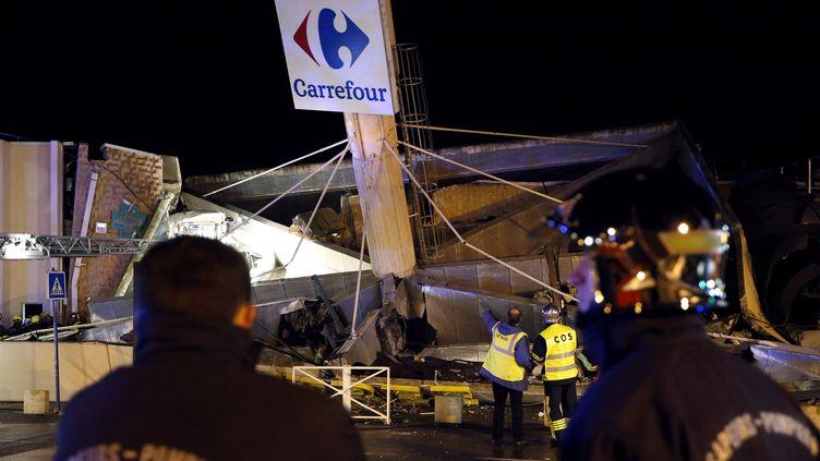 Des pompiers en face de l'hypermarché Carrefour de Lingostière, à Nice (Alpes-Maritimes), après l'effondrement d'une partie de son toit, le 5 février 2014. (VALERY HACHE / AFP)