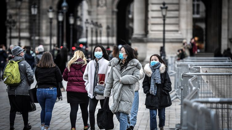 Des touristes portent un masque de protection pour se prémunir du nouveau coronavirus Covid-19, le 28 février 2020 à la Pyramide du Louvre, à Paris. (STEPHANE DE SAKUTIN / AFP)
