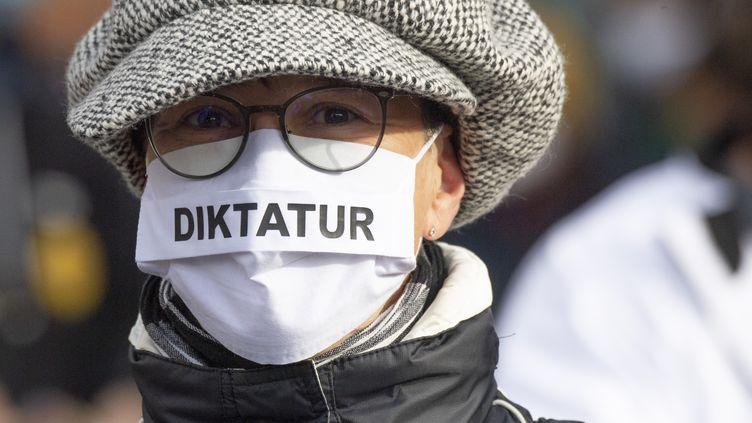 """Une manifestante portant un masque sur lequel est inscrit le mot """"Diktatur"""" (""""dictature""""), lors d'une manifestation à Francfort (Allemagne), le 14 novembre 2020. (BORIS ROESSLER / DPA / AFP)"""