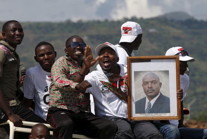 Des partisans du président burundais, Pierre Nkurunziza, paradent avec son portrait, le 15 mai 2015, dans la capitaleBujumbura (Burundi). (GORAN TOMASEVIC / REUTERS)