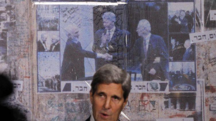 Le secrétaire d'Etat américain John Kerry à Tel Aviv (Israël), le 5 novembre 2013, devant une photo de la célèbre poignée de mains entre King Hussein etYitzhak Rabin sour le regard de Bill Clinton. (JASON REED / REUTERS)