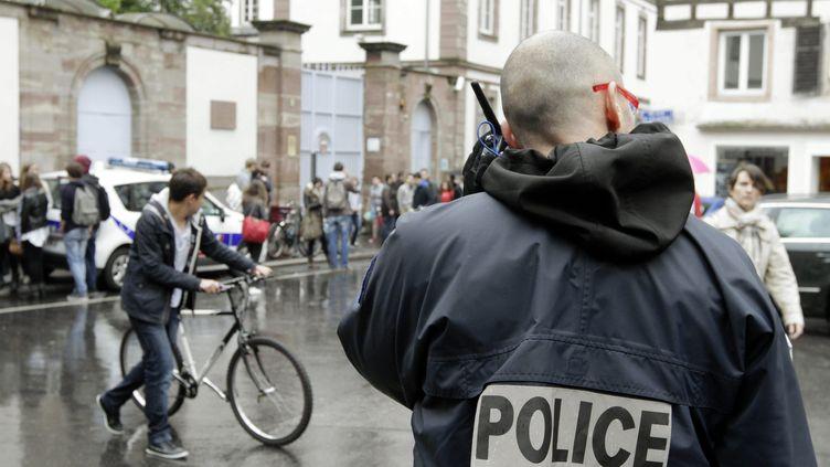Un policier surveille l'entrée d'un lycée de Strasbourg, le 17 mai 2013. (MAXPPP)