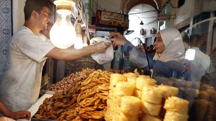 Une femme achète des pâtisseries traditionnelles pendant le ramadan, à Tunis, le 2 juin 2017. Image d'illustration. (MOHAMED MESSARA / EPA)