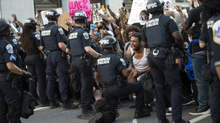 Un policier agenouillé face àune foule manifestant contre la mort de George Floyd, le 31 mai 2020, à Washington DC (Etats-Unis). (ROBERTO SCHMIDT / AFP)