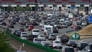 Des voitures coincées dans un embouteillage au péage de Villefranche-sur-Saône (Rhône), le 18 juillet 2015. (PHILIPPE DESMAZES / AFP)