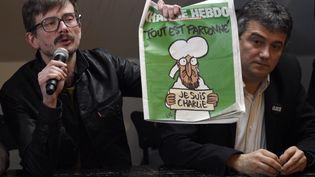 """Le dessinateur Luz (G) et le chroniqueur Patrick Pelloux présentent le premier numéro de """"Charlie Hebdo"""" à paraître après la série d'attentats, mardi 13 janvier 2015, dans les locaux de """"Libération"""", à Paris. (MARTIN BUREAU / AFP)"""