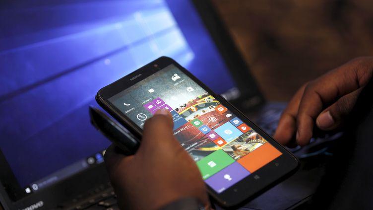 Le représentant d'une grande firme technologique américaine vérifie des applications numériques lors du lancement d'unnouveau système d'exploitationà Nairobi (Kenya), le 29 juillet 2015. (THOMAS MUKOYA / X90150)