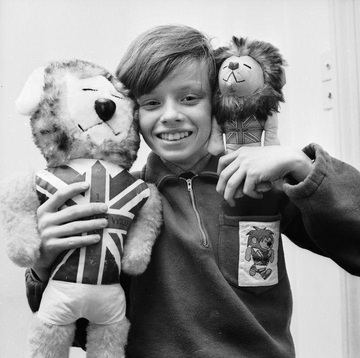 """Le fils du créateur de la mascotte de la Coupe du monde 1966 avec des peluches """"World Cup Willie"""", en février 1966. (JOHN PRATT / HULTON ARCHIVE / GETTY IMAGES)"""