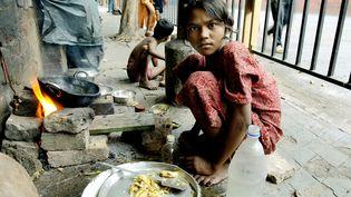 Une enfant se prépare un repas à Calcutta (Inde), en 2006. (DESHAKALYAN CHOWDHURY / AFP)