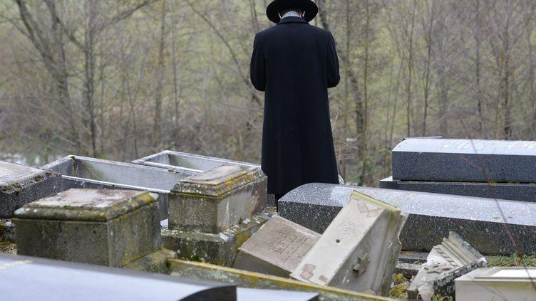 Un rabbin prie devant des tombes juives profanées dans le cimetière de Sarre-Union (Bas-Rhin), le 17 février 2015. (MAXPPP)