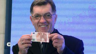 Le Premier ministre lituanien,Algirdas Butkevicius, retire un billet de 10 euros, le 1er janvier 2015, à Vilnius (Lituanie). (PETRAS MALUKAS / AFP)