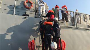 Des migrants secourus en Méditerranée montent à bord d'un navire de la marine maltaise, le 23 août 2019. (ANNE CHAON / AFP)