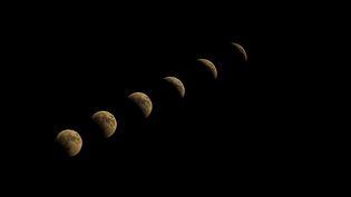 La Lune, pleine, est peu à peu rentrée dans la pénombre, puis dans l'ombre pour se retrouver totalement dans l'ombre, avant d'en sortir progressivement. Ce montage a été réalisé à partir de prises de vue réalisées à Ankara (Turquie). (ALI BALIKCI / ANADOLU AGENCY / AFP)
