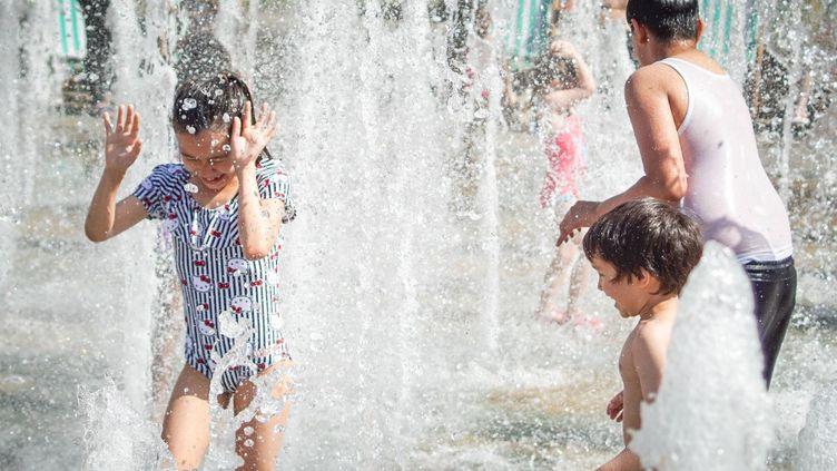 Des enfants jouent dans une fontaine, au Peace Garden de Sheffield en Angleterre, le 25 juillet 2019. (GIANNIS ALEXOPOULOS / NURPHOTO)
