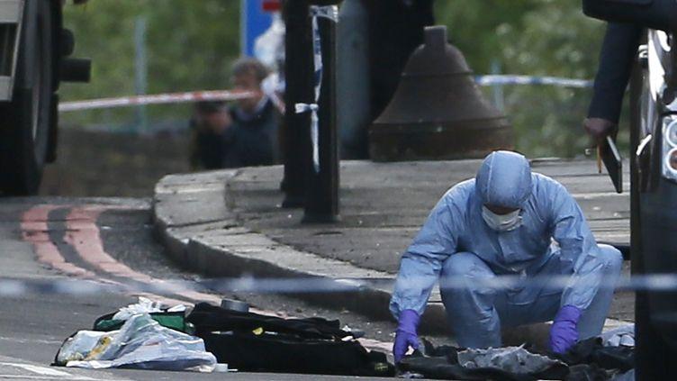Un enquêteur de la police britannique relevant des indices sur les lieux de la violente attauqe durant laquelle deux hommes ont tué un soldat à coup de machette, mercredi 22 mai à Londres (Royaume-Uni). (STEFAN WERMUTH / REUTERS)