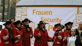 """Des femmes costumées devant un """"point sécurité"""" pour les femmes pour le carnaval de Cologne (Allemagne) le 3 févrizer 2016. (WOLFGANG RATTAY / REUTERS)"""