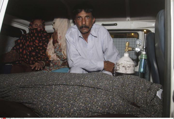 Mohammad Iqbal aux côtés de sa femme enceinte lapidée à mort, dans une ambulance, mardi 27 mai à Lahore (Pakistan). (K.M. CHAUDARY/AP/SIPA / AP)