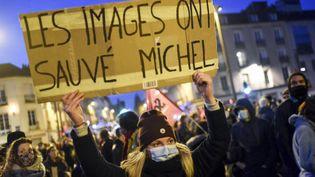 """Une femme tient une pancarte (faisant référence au passage à tabac du producteur Michel Zecler), lors d'une manifestation contre la proposition de loi """"sécurité globale"""", à Nantes, le 27 novembre 2020. (SEBASTIEN SALOM-GOMIS/SIPA)"""
