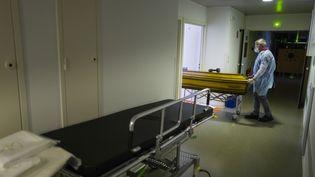 Un employé des pompes funèbres sort le cercueil d'une victime du Covid-19, le 5 avril 2020, à l'hôpital de Mulhouse (Haut-Rhin). (SEBASTIEN BOZON / AFP)