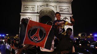 Les supporters du Paris Saint-Germain célèbrent la qualification en finale de la Ligue des champions avenue des Champs-Élysées près de l'Arc de Triomphe à Paris, le 18 août 2020. (GEOFFROY VAN DER HASSELT / AFP)