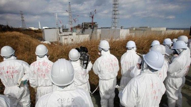 Des journalistes escortés par des employés de Tepco sur le site de Fukushima. (ISSEI KATO / POOL / AFP)