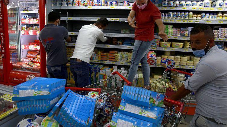 Des employés d'un supermarché d'Amman (Jordanie) retirent des produits français des étalages le 26 octobre 2020. (KHALIL MAZRAAWI / AFP)